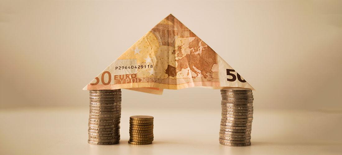 Billete en forma de casa y monedas. Símbolo de protección al empresario